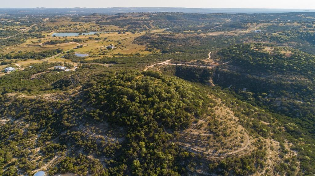 Stunning, long range Hill Country Vistas from this private 26.5 acre hill top in one of the most prestigious communities in Blanco, Ranches of Brushy Top. A level build envelope at 1680'± above sea level awaits a custom designed home featuring dramatic hill country and lake views, encompassed by mature oaks. The unique topographical formation of this property features its own look out peninsula at 1600' +/-. Underground utilities and access to high speed internet available. Behind the gates of Ranches of Ranches of Brushy Top, you'll find an impressive 1-D-1 Ag-exempt, luxury ranch community dedicated to the preservation and appreciation of native and exotic wildlife. Elk, Lechwe, Black Buck, Sika, Oryx, Rio Grande Turkey and more roam freely and graze on native grasses. Community amenities include controlled access, a 9+/- and 13+/- acre stocked lake offering excellent fishing, swimming and kayaking paired with miles of trails for riding, hiking or cruising in your UTV throughout an 80± acre nature preserve.