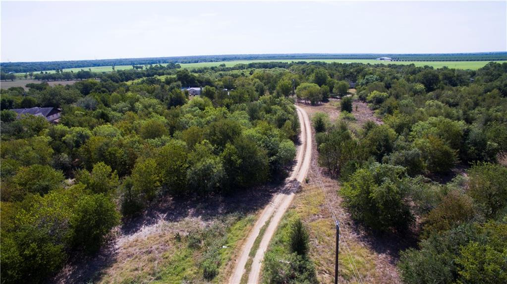 12.034 AC Unrestricted! AG exempt! Water well in place. Electricity in place. Long drive leads to a beautiful homesite with large mature trees.  No floodplain. This property could be cleared to leave privacy from the road, but look like a park. Tract to the right is also for sale.