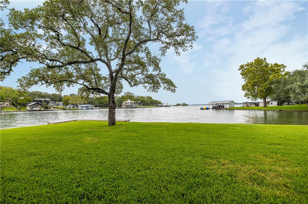 Desirable Blue Lake Estates, stand-alone Lake LBJ waterfront townhome! 3/2.5 all on main floor with amazing loft set up as bunkroom/gameroom. Beds sleep10! Crown molding, vaulted ceilings, granite and tile, open concept plan, owner's suite separate from guest suite. Indoor and outdoor space for large family gatherings! Souring high ceilings in the great room with a beautiful stone fireplace, enjoy all seasons at this constant level lake. Covered patio overlooks the water with towering trees that afford shade when you aren't on the water. Spacious yard for croquet, throwing the football, bocce ball, spike ball and more! Walking distance to basketball and volleyball courts! Gorgeous lawn gently slopes to the water! Boat house includes boat lift and 2 personal watercraft ramps. Exceptional storage includes 2 car attached garage with golf cart garage which houses all of the water toys! Calm waters perfect for paddle boarding and kayaking and swimming! Blue Lake offers golf course, neighborhood parks, tennis courts, and more. This entertainer's property can come fully equipped for you to step immediately into making lifetime memories.  Low maintenance, Lakeside HOA covers sprinkler system, lawn and common area maintenance. Legally described townhome, but no connecting walls. Come see today!