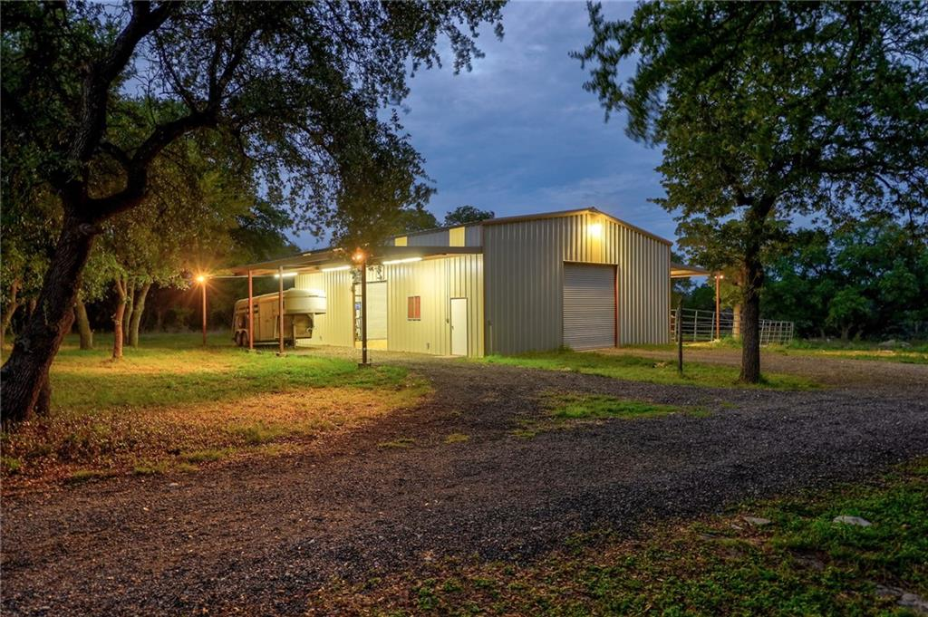 Lovely 5 acre ranchette! Rare and highly sought-after location a few miles outside of Liberty Hill and just 5 miles from Hwy 29. You will not find a property with more gorgeous live oak trees than this one! Lightly restricted, bring your horses (up to 10)! Large barn/workshop/equipment-storage area with a 16' overhang on each side for your livestock to shelter or for covered parking. Livestock paddock and round pen. Property is easy to access with trailers or that RV and has a beautiful and functional circle drive. The home features a full-length front porch, upgraded bathrooms, a brick wood-burning fireplace in the family room, and an eat-in kitchen. Propane tank on property for gas stove and water heater. Schedule a showing today!