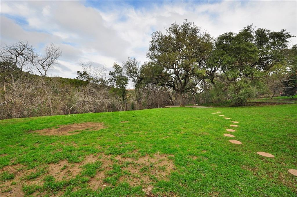 """Live now and make plans to remodel or add on--ranch home on huge .65 acre lot in great pocket area.  All the lots in this pocket are .50 acre.   Feels very """"country in the city"""".This lot will have amazing views of the canyon wall above Bull Creek w/some tree clearing at back of lot. Adjacent to Bull Creek park-with miles of hiking trails--literally in your backyard. Large flat build area, w/1 heritage tree @ front corner. Lots of new construction in 2m plus range on the street."""