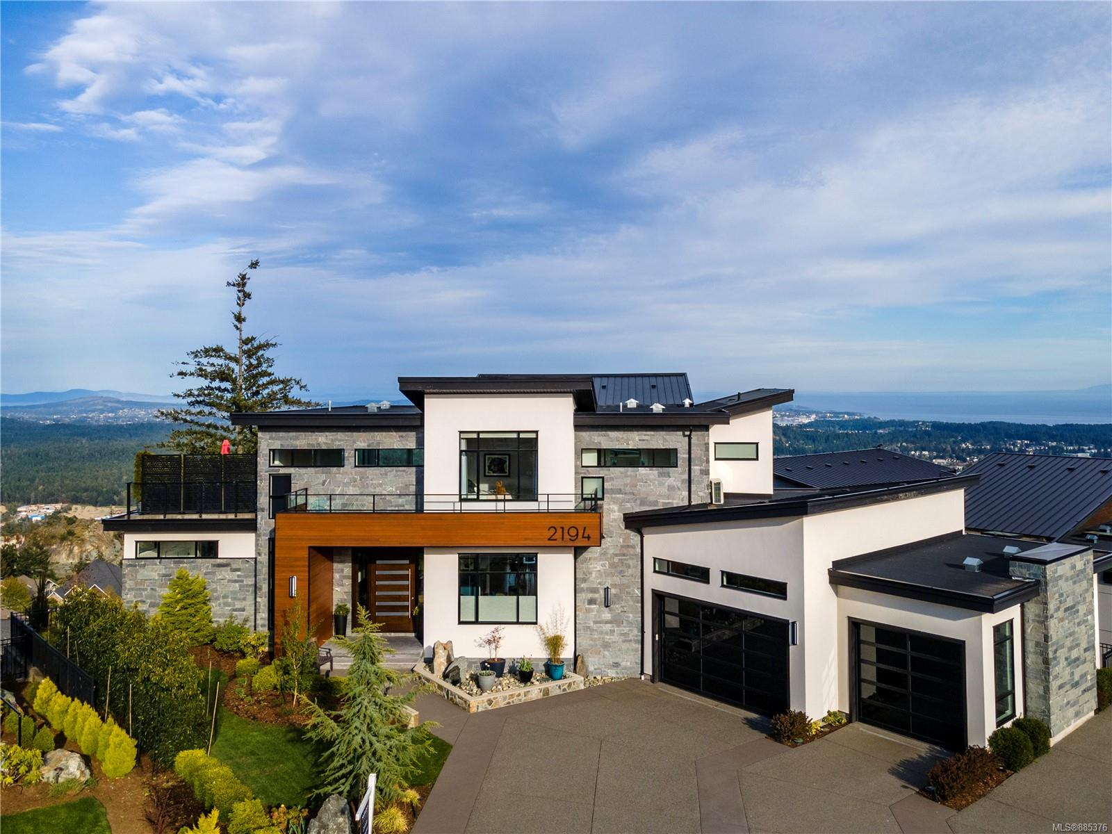 Contemporary, Custom, Pristine…this show-stopping 5BED/6BATH Bear Mountain property is situated at the end of a quiet cul-de-sac on Navigators Rise. Breathtaking 270 degree views of Juan De Fuca Strait, Peninsula & Olympic Mountains from 3 south facing decks + 2 patios. Through the oversized pivot door, you'll experience 5,600SQFT of open-concept living boasting 22' vaulted ceilings + oversized windows to elevate the scenery. Entertain in luxury from the chef's kitchen with urban cultivator, gas range & fully equipped prep kitchen. Make your way up the floating staircase to the Primary Suite with deck ft 180 degree views, separate dressing area, water closet, soaker tub & spacious walk-in shower. Lower level includes media/rec room with ample bar, wine cellar w/cooling options, 2BEDS & professionally landscaped, irrigated & solar lit yard. Additionally, 3 car garage workshop, Lutron smart blinds, RV/Boat pad, security system & MUCH more. Experience this impressive dream home yourself!