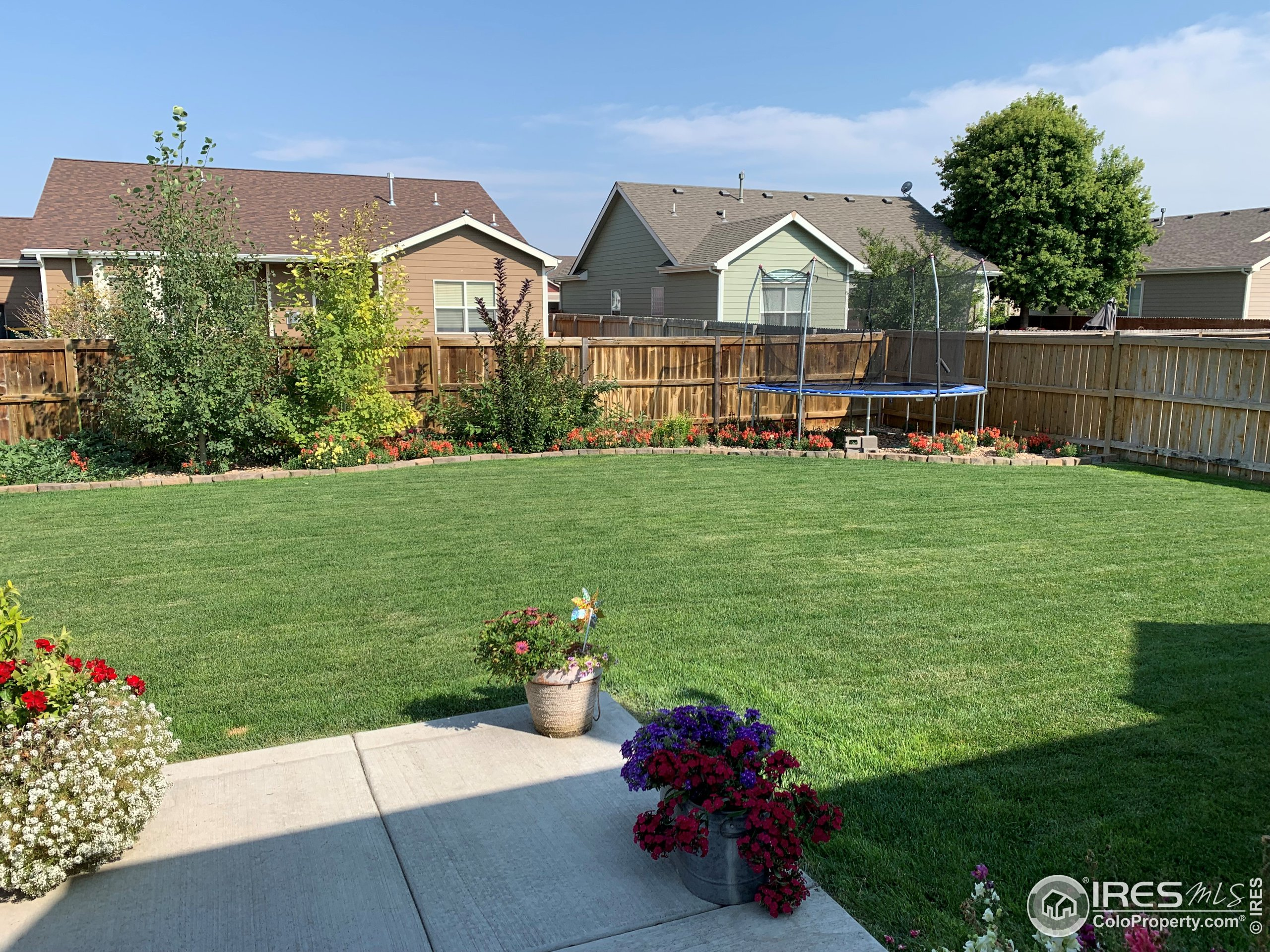 Backyard is full of flowers, plants, and garden sections along with lush green grass