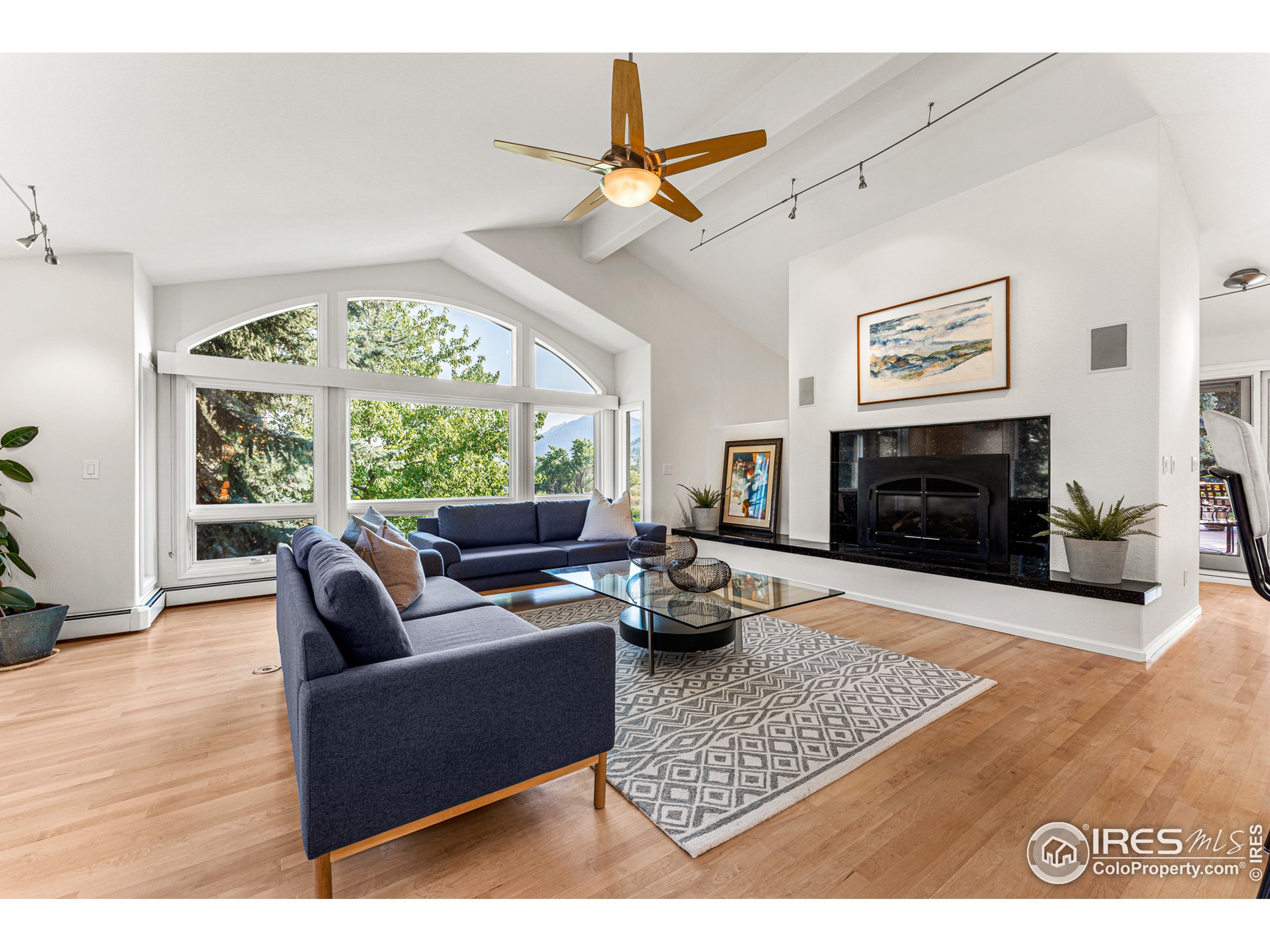 An open floorplan with valuted ceilings, sitting hearth and gas fireplace