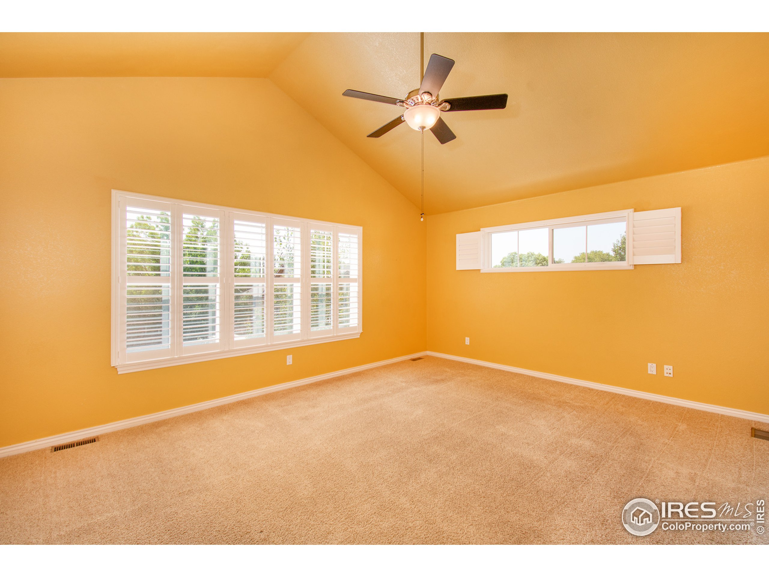 Huge  Primary Bedroom w/vaulted ceilings and plantation shutters
