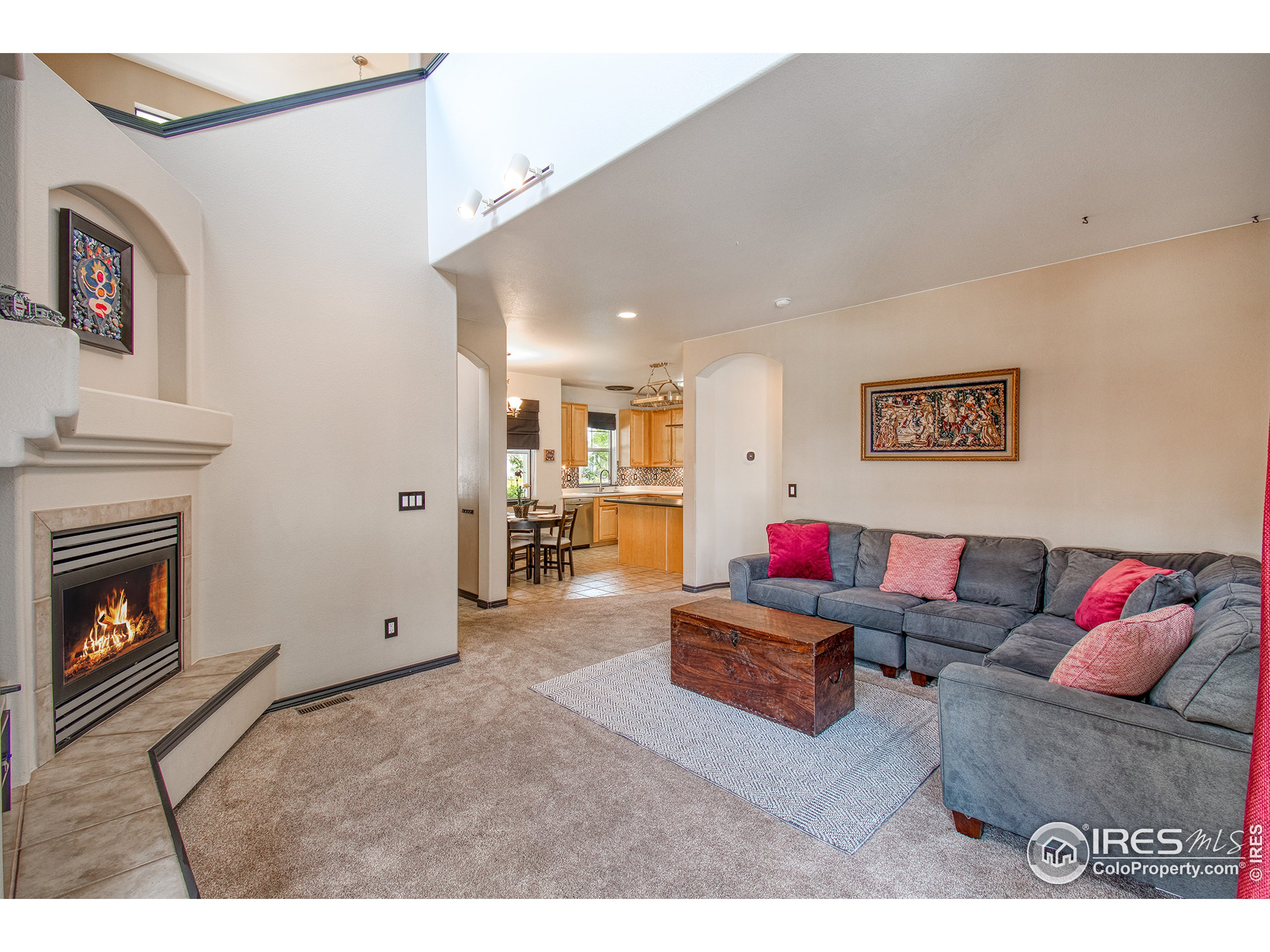 Living room features high ceilings and cozy fireplace