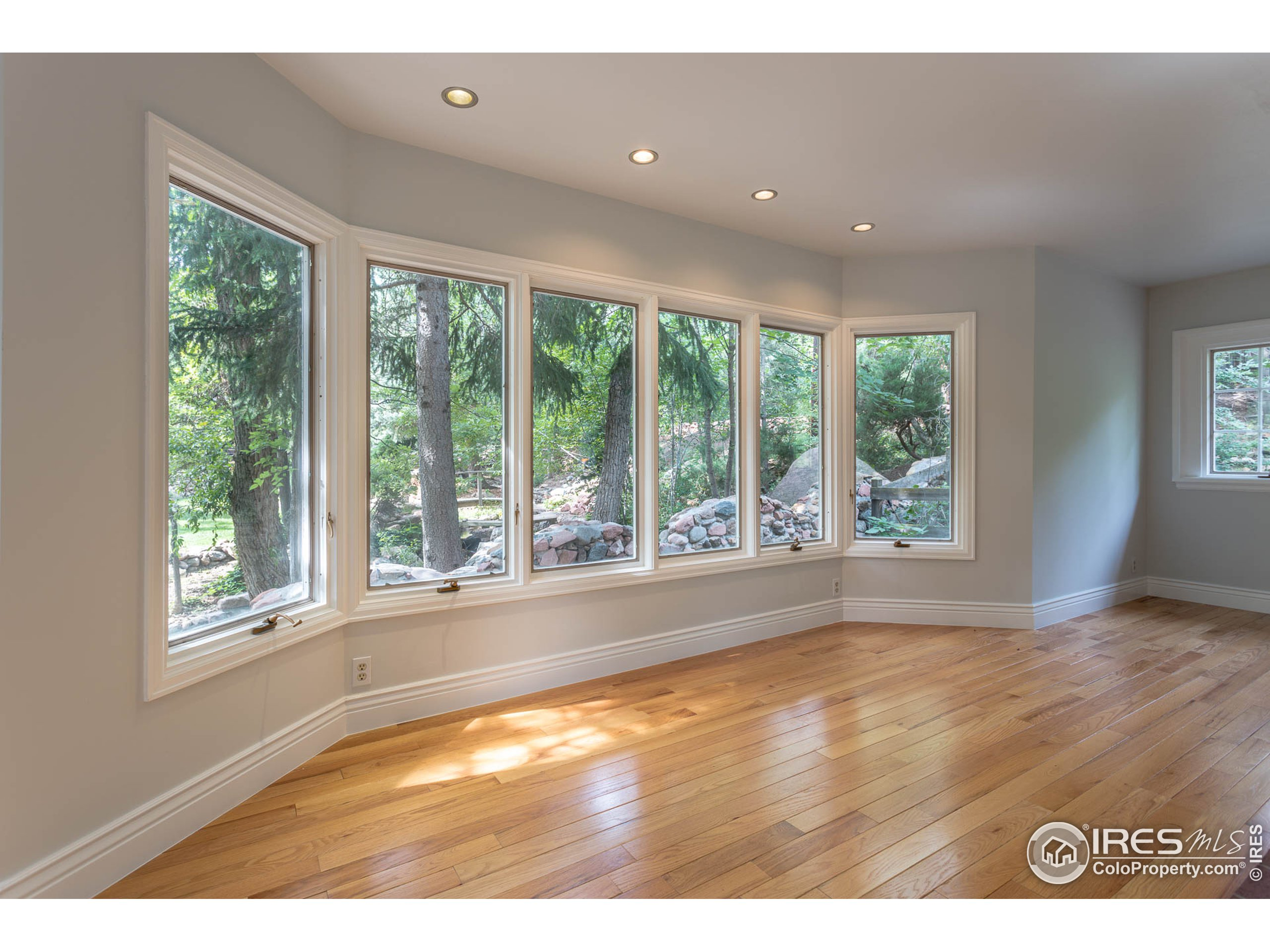 Office with large windows facing serene Gregory Creek