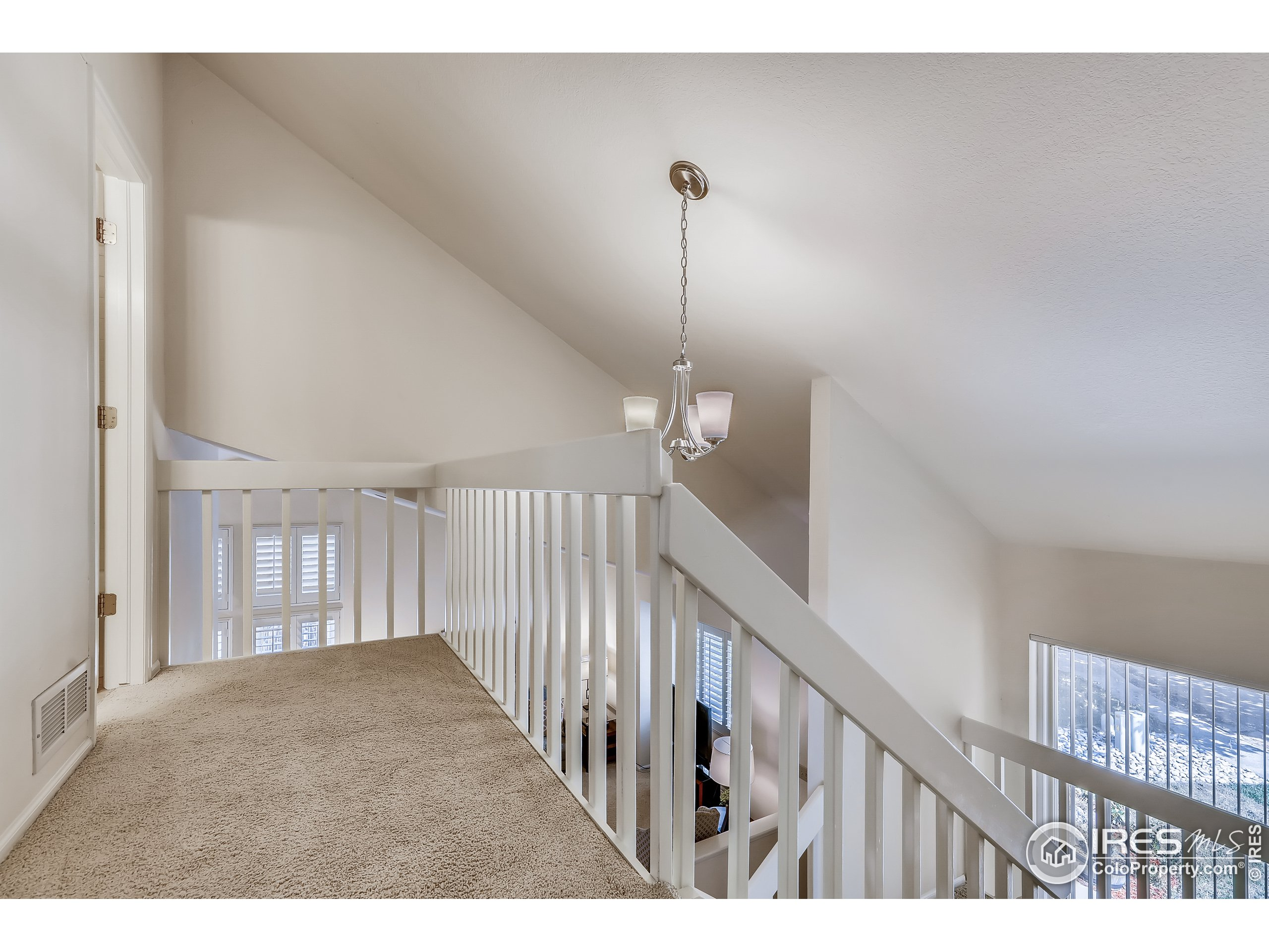 Upstairs landing featuring vaulted ceiling.