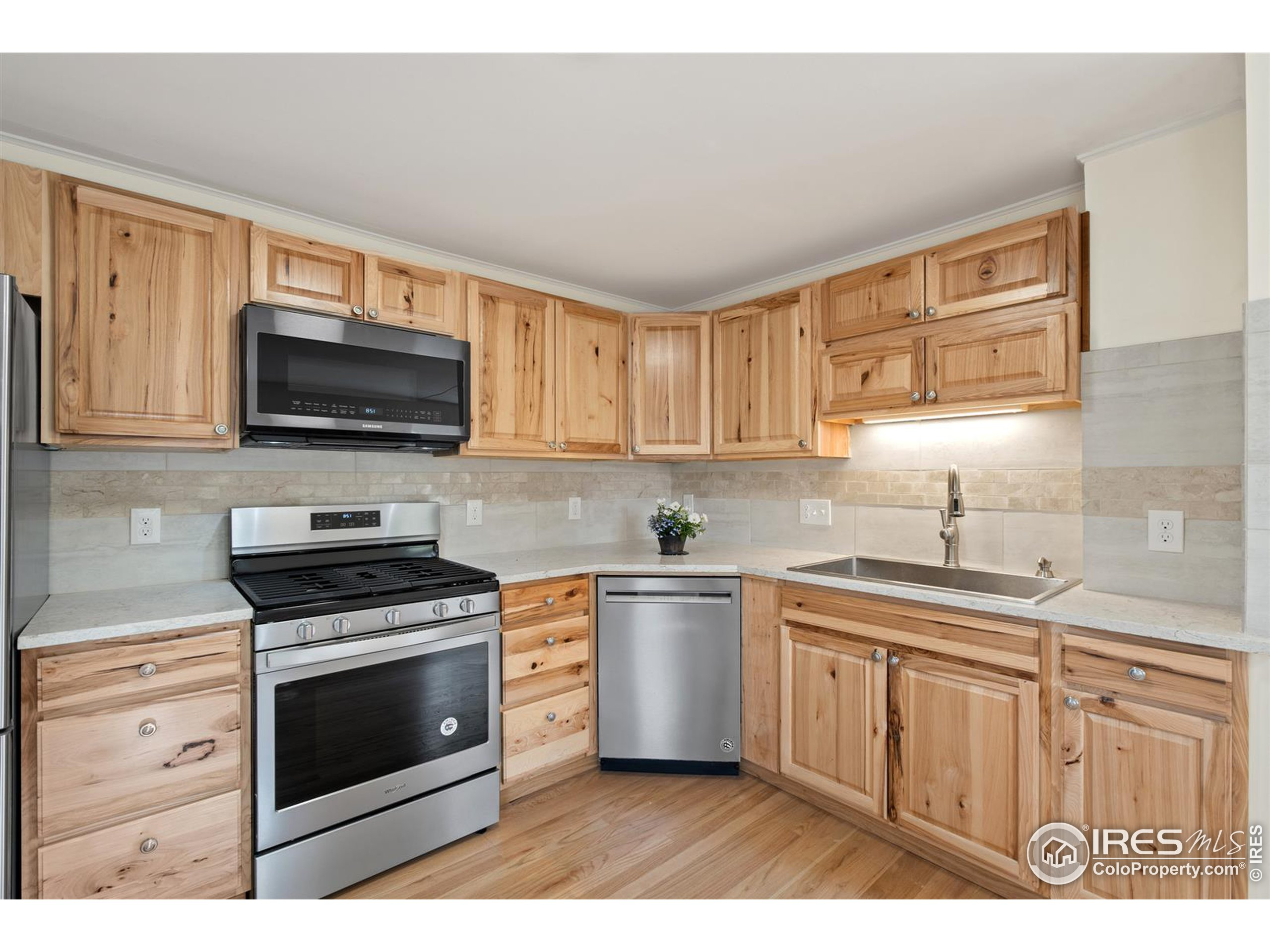 Gas range, stone counters, and beautiful raised-panel cabinets