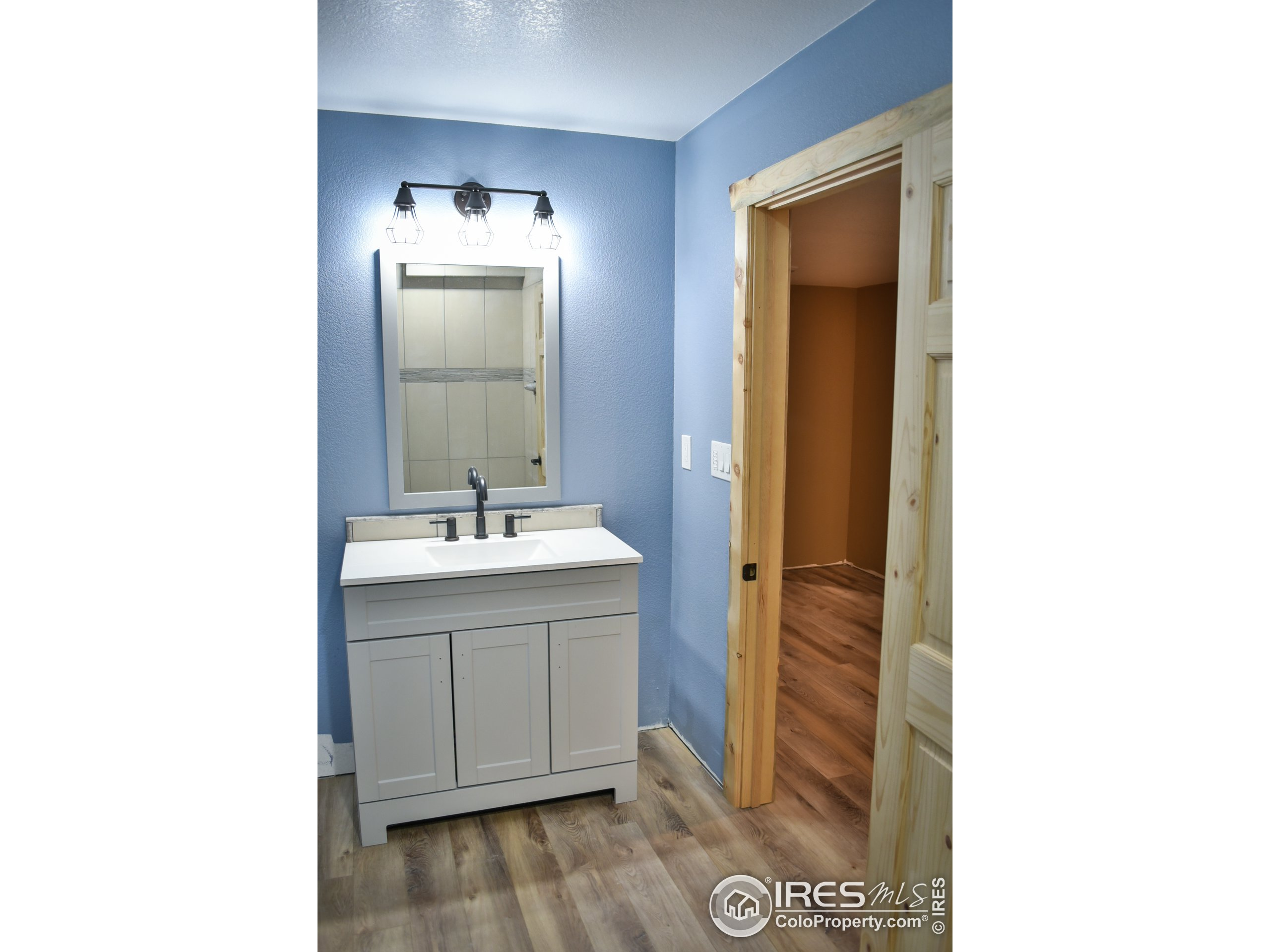 Basement laundry area, with view to 3/4 bath and 2 storage/office areas.