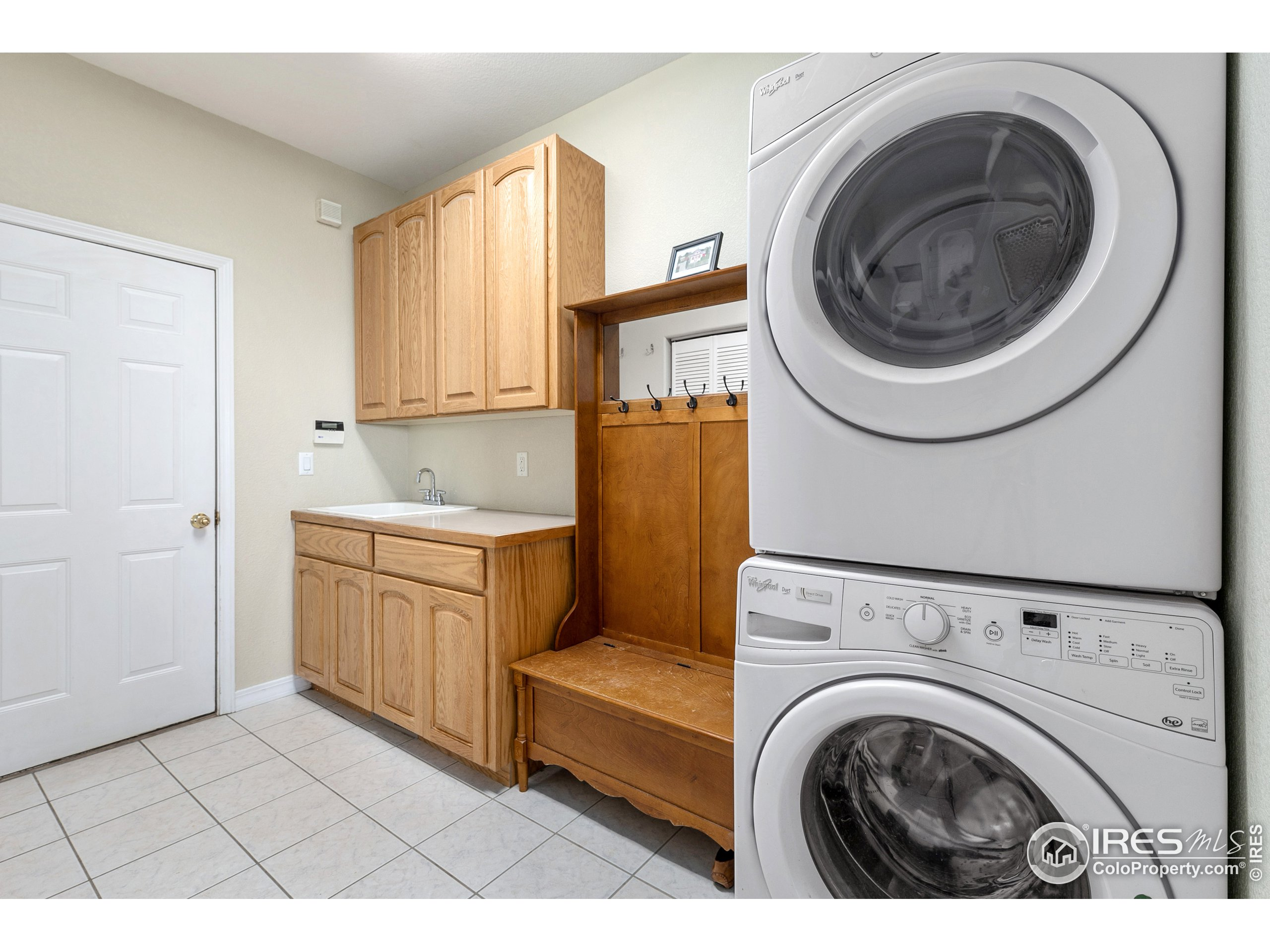 full laundry room with sink, cabinets, counters and closets for storage