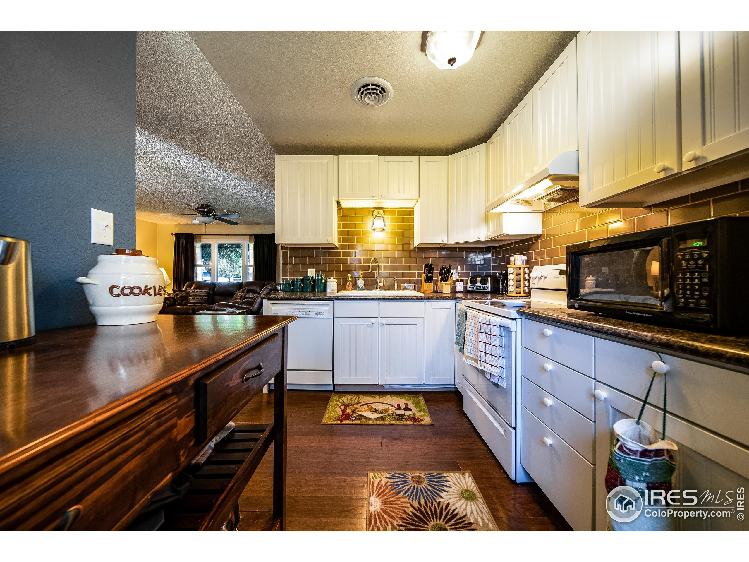 The flooring, counter tops, and subway tile backsplash, are the perfect contrast to shaker style cabinets.