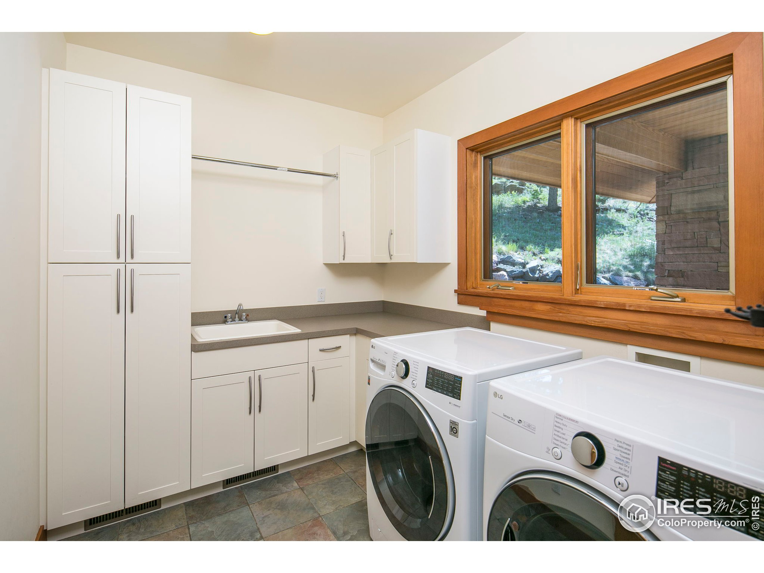 main floor dedicated laundry room with additional sink and storage