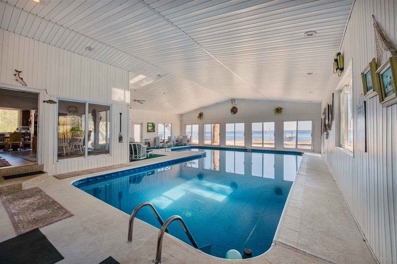 This home is truly one of a kind and comes with almost 2,000 square feet of indoor pool!! Situated on the end of a private road cul-de-sac with 138 foot of Blackwater Bay frontage AND frontage on Alligator Bayou. Features 3 bedrooms, 4 full baths and 2 bonus rooms! Bonus room 1 is on the first floor just off the entry way and could easily be converted into a bedroom. Bonus room 2 is on the second floor which leads to two additional bedrooms and a full bath. This section can be completely closed off for the kids or visitors! The master bedroom sits towards the rear of the home with a balcony overlooking the bay, has a huge walk in closet, walk in shower with 2 showerheads, Jacuzzi tub and double vanity with sitting area. Home also features 2 living spaces, huge kitchen, formal dining, porcelain title throughout the first floor and custom ordered light fixtures. Out back, the property has 2 concrete retaining walls. One at the waterline and one buried in the ground midway in the back yard.