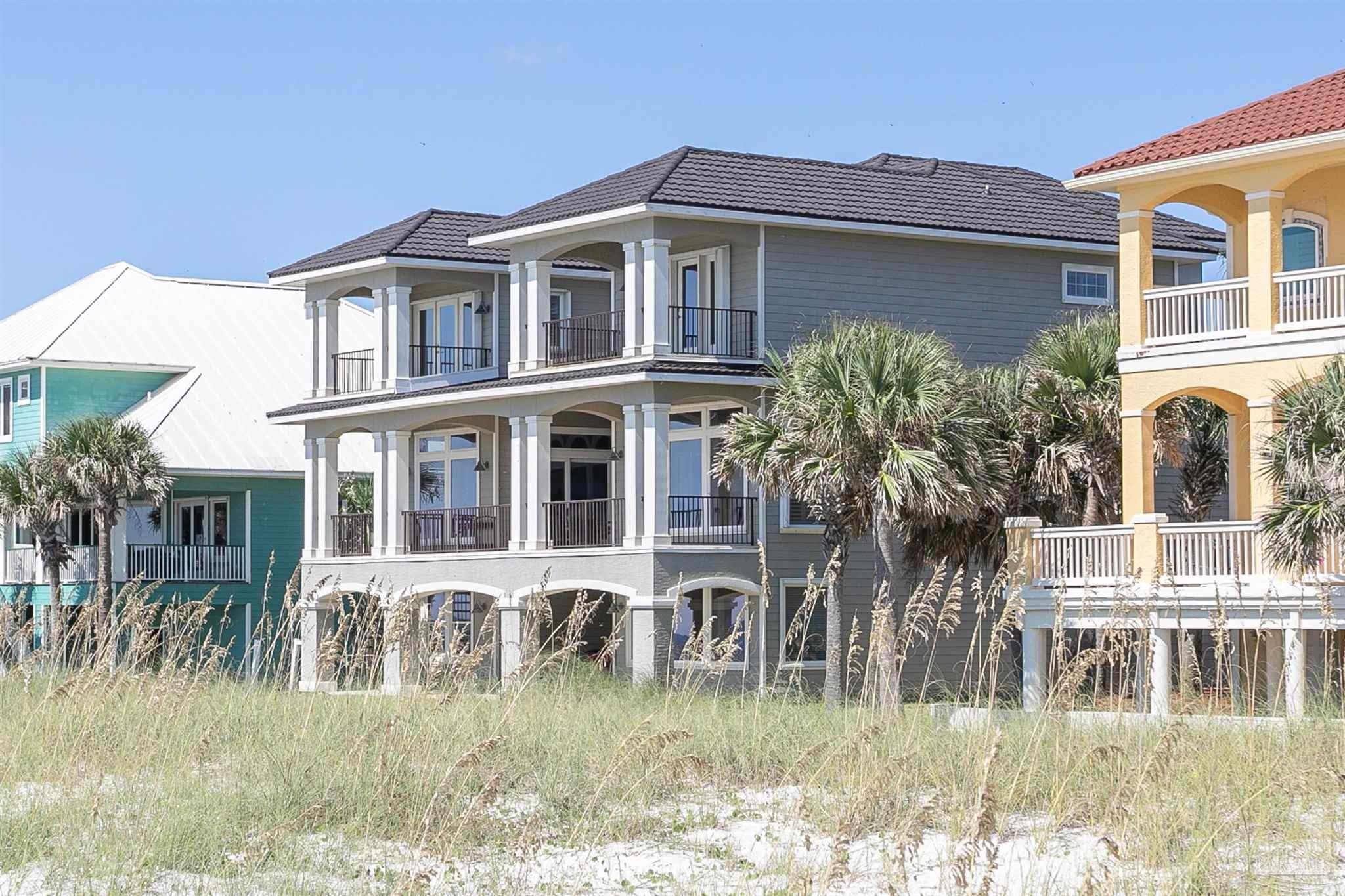RARE OPPORTUNITY FOR PRIVATE BEACHFRONT LIVING IN THE HEART OF PERDIDO KEY! Parasol East is a secure, gated non-rental gulf-front community that encompasses 900'+ of sugar white sand beaches and just a short walk to Johnson Beach and the National Seashore! This coastal charmer sits on 75' of beachfront and boasts 5 bedrooms, 5.5 baths on 3 floors with a custom elevator servicing all levels. The 1,400+ sq.ft. outdoor dining and relaxation areas with deep covered porches allow for maximum privacy and unobstructed gulf-views! The open main living level is perfect for entertaining with views from every room, featuring hardwood floors, 10ft ceilings, and an abundance of natural light! The living room is complete with wet bar, wine cooler, and ice maker! The kitchen exudes elegance with granite countertops, stainless steel appliances, 2 Bosch side by side ovens, dishwasher, Viking 5 burner stove, commercial grade exhaust accentuated by stunning mantle and tumble marbled detailing, Rohl nickel faucets, 8' wide custom pantry, oversized granite island with prep sink, and bar seating which allows guests to join the kitchen experience. Tucked behind the kitchen is a quiet nook perfect for an office! The main level has a secluded 2nd master suite with en-suite bathroom tucked away for extra privacy. The exquisite custom curved staircase leads to a 3rd level living area, 2nd office, master suite and 2 guest suites. Gulf front master suite includes private covered porch, his/hers closets, en-suite bath, steam shower, dual vanities, and luxury spa tub. The 1st Floor family/game room is where all the fun happens after a long day at the beach! Guests and family can enjoy the tv room, kitchenette, large guest bedroom/bath and add'l full bath - leading outside to outdoor covered patio just steps from the sand. Come home to this amazing beach getaway where paradise awaits!