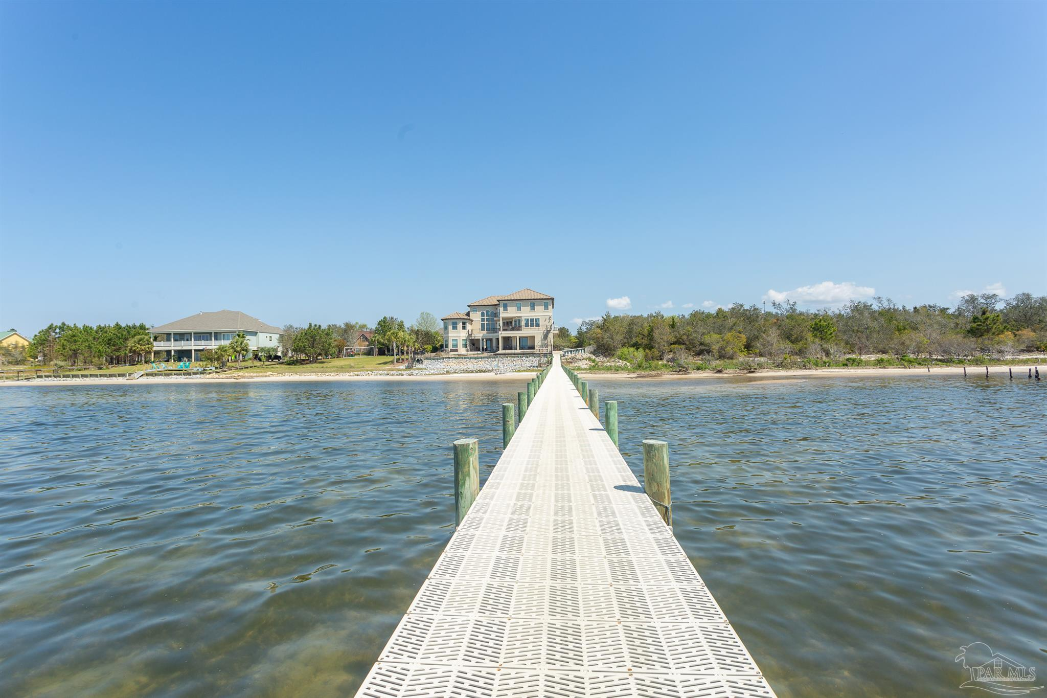 The water is always in view—and in reach—in this 9,400 square foot, six-bed, seven-bath custom-built home in one of Navarre's most coveted gated communities. Relax and enjoy the breathtaking sights of Santa Rosa Sound from the wraparound second-story balcony overlooking a spacious ozone-filtered pool and hot tub. A spiral staircase leads to the multi-level patio, providing access to your own private beach and dock, perfect for spur-of-the-moment outings by boat, paddleboard, or jet-ski.  Need a break from the sun? Your three-row home theater with surround sound is the perfect place to cool down. The spacious home gym has room for all your equipment, plus a mirrored wall and large sliding glass doors overlooking the pool and sound. On the main level, the great room offers stunning views of the water through arched two-story windows, complemented by a marble fireplace with ceiling-height over mantel. Between the 273-bottle wine cellar and chef's kitchen with granite countertops, stainless steel appliances, custom vent hood, and dual ovens, you'll always be ready to entertain. Live the salt life in style! Call me to schedule your showing today.