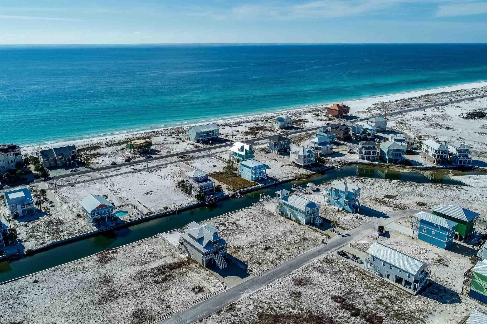 """View Builder's Model Home at 7407 Grand Navarre. 7395 Gulf Blvd is a To Be Built home. Build """"the ultimate"""" beach home that sleeps 15! To be built with 5 bedrooms, 5 1/2 baths, 3-stop elevator and wide balconies.  Inviting beach home to be built with 180mph fortified construction, upgraded with many designer features that include high 9-ft and 10-ft ceilings with an abundance of recessed lighting, wood plank porcelain tile throughout, custom wood work, double-step cottage ceiling, crown molding throughout, custom crown trim above all windows and doors, framed windows, tall eight foot doors, 3'' plantation blinds throughout, tall baseboards, hardwood stair treads and handrails, and brushed nickel hardware.  Well designed open concept floor plan has large family room that opens to the dining area,  and kitchen.  Both areas have tall extra wide sliding doors bringing in natural light and open to the wide balcony.  The cook will enjoy the spacious kitchen with tall solid wood soft close cabinets, under cabinet lighting, decorative glass fronted cabinets, upgraded granite and stainless steel appliances that include the refrigerator.  The first living area has a powder room, a laundry room that includes washer and dryer and two guest bedrooms, each with their own bath.  The second living level has a second family room with extra wide sliding glass doors to the balcony, second laundry and two guest bedrooms, each with their own tiled bath.  The spacious master bedroom has room for sitting area, recessed lighting, extra wide sliding glass doors to wide balcony, two walk-in closets and master bath with floor to ceiling tiled custom shower with niche shelves and two vanities.  On the main garage level, there is tandem parking for two or three vehicles, additional parking for a small vehicle or golf cart, and an additional open storage area.  Walk to the Gulf of Mexico, the Santa Rosa Sound and the Gulf Islands National Seashore!"""