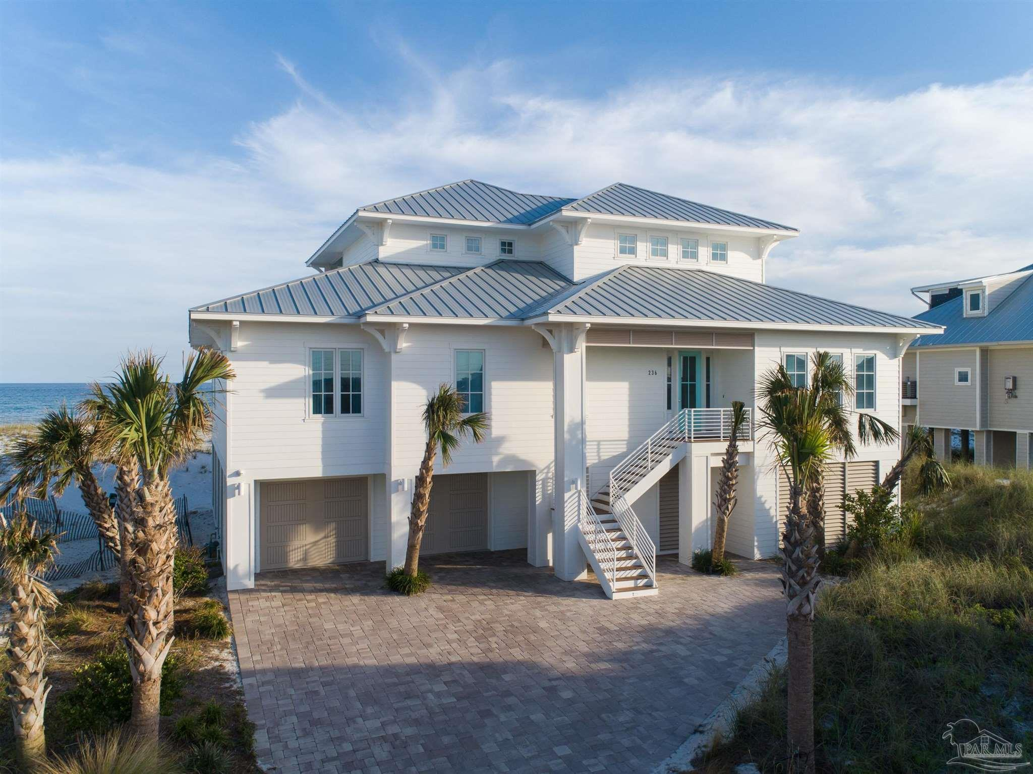 """Experience the luxury of a 30A-inspired home within the peaceful Pensacola Beach community, which was named the """"Most Beautiful Place in Florida"""" by Conde Nast Traveler. This coastal paradise will fuel your desire to leave the crowds and traffic of neighboring towns behind you. As you step into this professionally designed home, you're greeted by breathtaking Gulf of Mexico views and elegant finishes highlighting the coastal shiplap throughout. The open concept living area is flanked by a wall of windows overlooking the sugar-white sand beach and emerald waters, providing a wonderful space to entertain. Enjoy gorgeous views while preparing meals in the chef-style kitchen, featuring an island with seating for 4, inset cabinetry, quartz countertops, SubZero refrigerator, 6-burner gas range, and double oven. Just off the kitchen is a large walk-in pantry where you'll find a full-size freezer. The dining area comfortably seats 12, and the entire living space offers easy access to the expansive covered balcony. The master bedroom suite is a private oasis with direct access to the gulf-front balcony and the en suite bathroom includes double vanities, marble countertops, soaking tub, glass-enclosed shower, and large walk-in closet. On the 1st living level you will discover 3 additional bedrooms which all have their own en suite bathrooms, including a secondary gulf-front master suite. On the 2nd living level, discover another gathering room with built-in bunkbeds, living area, wet bar with beverage refrigerator, and access to a second gulf-front balcony. Two bedrooms are on either side of the living space, one being a gulf-front junior master with en suite bathroom. A full-size bathroom completes this living space. On the sand level, enjoy beach living with your very own Tiki bar and ample space to store cars, golf carts and all your beach toys. This luxurious turn-key Gulf-front property will be a wonderful primary residence, second home, or successful vacation rental."""