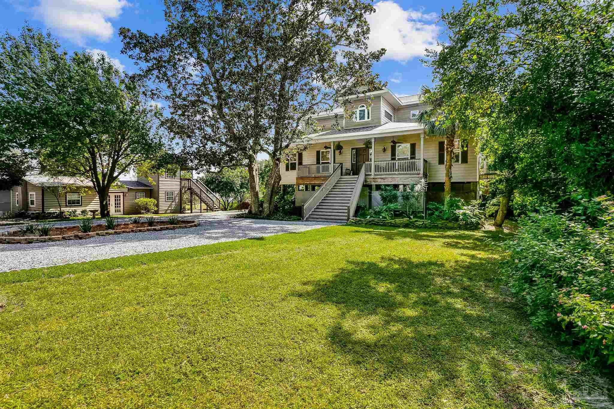 """Rarely do you see a more beautiful setting that is over an acre on the Intracoastal Waterway with 144 feet of beach.  This 4 bed 2.5 bath home has so much to offer.  The entire 2nd floor (living area) has 18 inch travertine throughout, energy-efficient blinds that cover all of the windows and a view you won't believe.  From the foyer you walk into the living room w/wood burning fireplace, that leads into the kitchen/dining area.  The kitchen features a commercial grade Wolf range with 2 ovens, 4 burners, a grill and a griddle.  It also has a commercial grade Wolf exhaust fan and a pot filler.  There is a breakfast nook and a breakfast bar.  The sellers are currently using the formal dining room as an office.  Across the entire back of the house is a covered deck that has a hot tub an outdoor cooking area and a great view of the sound.  Upstairs has an oak staircase and oak floors in the common area.  The two very large bedrooms have carpet and window storage boxes with upholstered sitting areas for reading/relaxing.  The third bedroom is currently being used as an insulated music room with wood floors. The exterior features an inground pool, sprinkler system,  5 fruit trees, many flowering trees and a hammock near the 144 of beach  If you are still not convinced....there is a guest house (could be used as an ABB) that is furnished, with 2 bedrooms, kitchen and laundry room.  Above the guest house there is an art studio. P.S. there is also a """"dumb waiter"""" in the main house so that you don't have to carry your groceries up the stairs."""