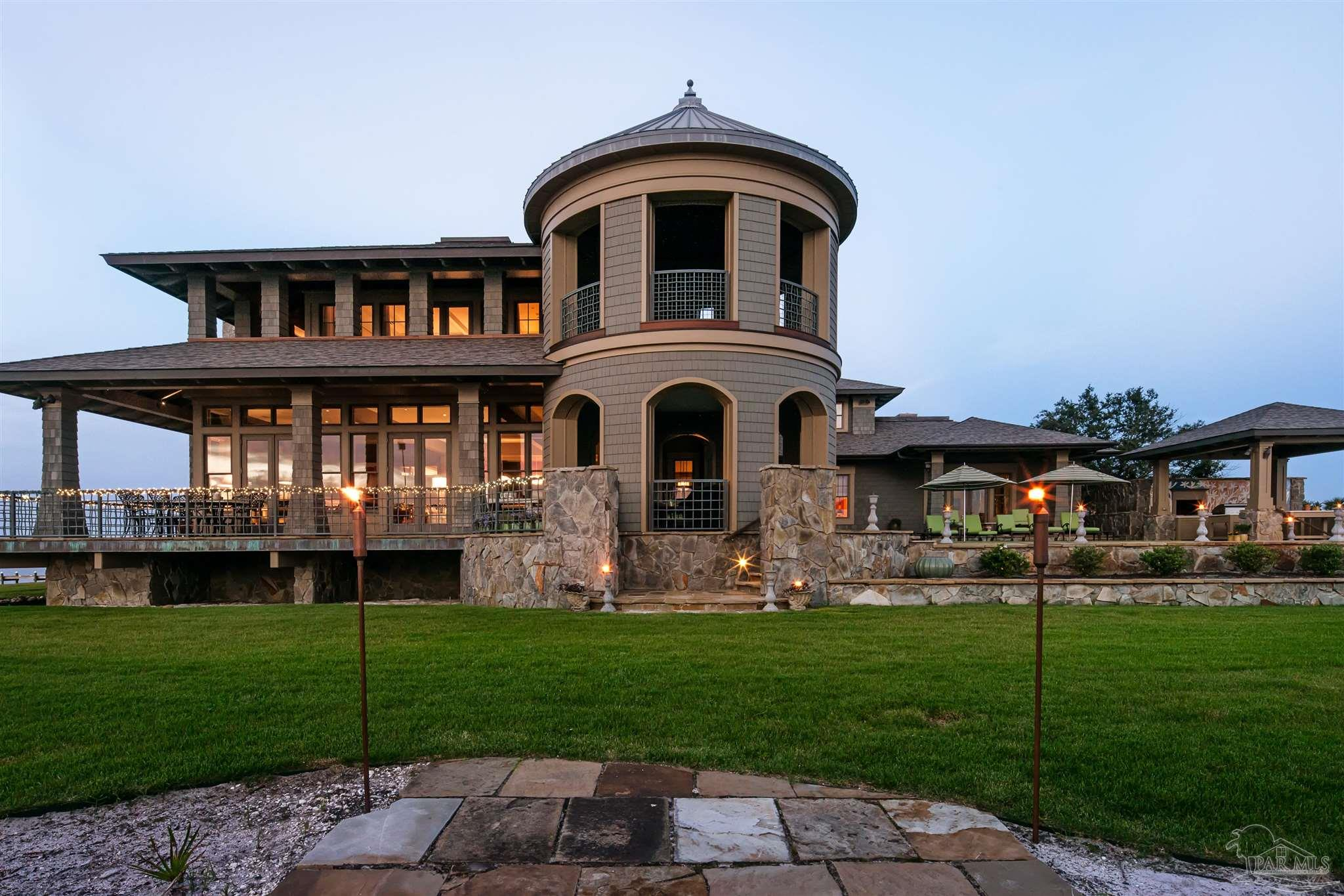At the Western tip of the Peake's Point Peninsula, sits 732 Peake's Point. The definition of luxury and elegance. This timeless beauty offers just under 12,000 square feet with breath taking 300° Views of Pensacola Bay and the Intracoastal Waterway - lively vistas in every direction make this home site the diamond in a sea of emerald.  Across Pensacola Bay, enjoy the passing of ships in and out of port and the sparkling lights of downtown shimmering on still night waters. This home's location makes it a great place to watch the US Navy Blue Angels team fly in their tight formations during seasonal practices. To the southwest, on a clear day, you can see historic Fort Pickens and the city of Mobile, Alabama beyond. Views of Pensacola Bay to the north and Santa Rosa Sound to the South. And of course serene sunsets to the west. Enjoy walking and fishing from your 1000+ feet of beach and shore line, or take your boat out to the Gulf only minutes from your dock. This home is situated in a private and gated community of only 20 properties. 732 Peake's Point is at the pinnacle of the small enclave.  Attention to every detail was paid in the creation and construction of this Private Waterfront estate. The owner Poured over the details and searched both local and international artisans to create and incorporate all the features, finishes and stunning accents.  Some of the details: GeoThermal HVAC, Commercial grade elevator, whole house fire suppression system and a whole house generator. Custom designed bronze handrails on the 5000 sq. ft. of porches. Handcrafted Sycamore wood walls in the office and Pear wood walls in the formal dining room. Wayne Dalton Garage doors. Anderson high impact windows. finished off with Spanish cedar shake exterior and a salt water pool.  Come home to your own private oasis and enjoy sunrise and sunset at this truly one of a kind estate.