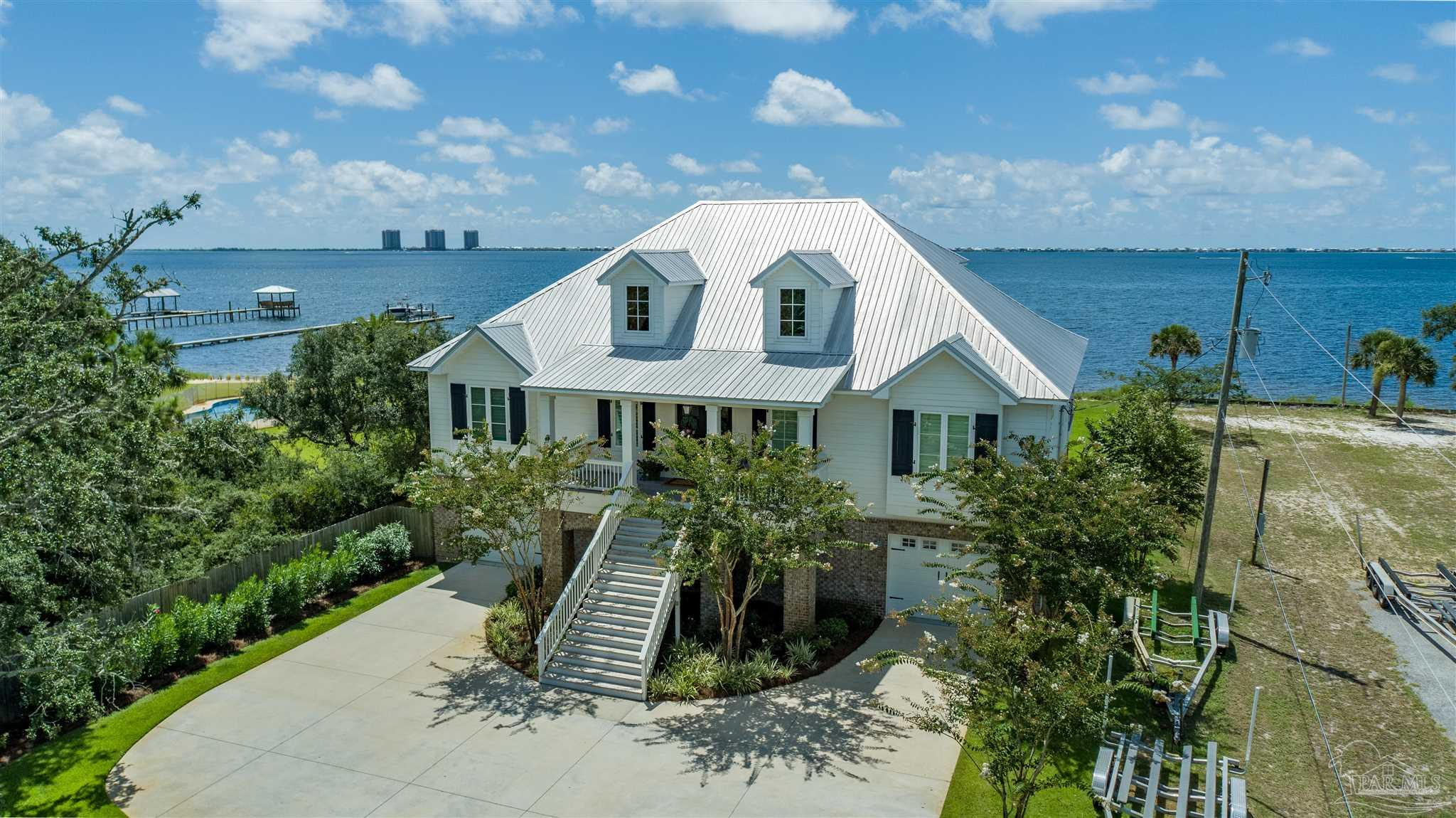 """Soundfront living at its finest, come enjoy everything the coastal lifestyle has to offer! This precision craftsmanship custom home is situated among beautiful trees on a large lot with access to your own soundfront private beach. This stunning home embraces serene living and offers many upgrades~outside has a large covered porch~private beach~long """"Thru-Flow"""" dock~electric boat lifts allows for convenient access to the Sound, intercoastal and Pensacola Beach located directly across~back and front yard irrigation system with well. Inside home has plantation shutters~elevator shaft for future elevator if needed~alarm system~Ring Doorbell~laundry with desk area~french doors with balcony access from living room, master bedroom and guest bedroom~all bedrooms with their own dedicated private full bath~master bath has double vanities, garden tub, separate shower, 2 closets 1 is a huge walk-in closet~half bath in hall for guest~beautiful open-concept floor-plan was thoughtfully considered to accommodate large gatherings for entertaining with family and friends~well designed kitchen with large island bar~quartz counter tops~walk-in pantry~double oven~gas cooktop~stainless steel appliances~spacious separate dining room to make entertaining easy and fun~beautiful wood like tile floors running through all the main living areas~high ceilings~built-in bookcases~gas fireplace in living room~upstairs offers a 4th bedroom~bonus room with bathroom~walk-in attic for easy storage access. There are multiple areas to enjoy gorgeous Soundfront views, fishing, paddle boarding, jet skiing, or just a relaxed pace of life. Don't miss out on all the charm that coastal living has to offer!"""