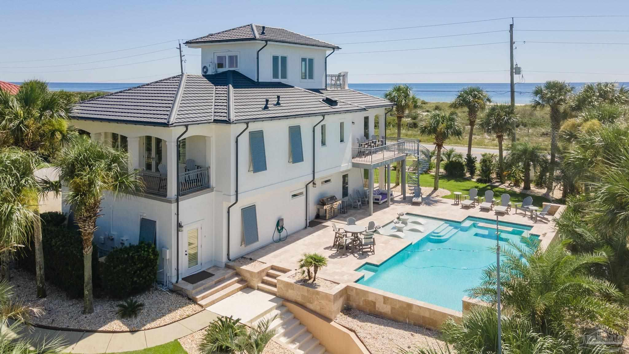 """""""ALL THAT"""" Perdido Key waterfront home is seeking a new owner to enjoy unobstructed beach & gulf views across miles of State Park Beach. The total coastal lifestyle includes boating from the deepwater boatslip/lift at the back door; lounging in the """"hollywood"""" style pool; long strolls on two miles of beach; breezy covered porches naps and memory making moments. Three stories of immaculately maintained and well planned space include a great room with custom cabinets and built-ins, porch access and a spiral staircase to the pool area.""""Chef's"""" kitchen complete with Thermador gas(propane) cooktop, deep fryer, steamer, Sub-Zero built-in refrigeration, convection/conventional oven with warming drawer & built-in microwave. Walk-in pantry. All closets and pantry have custom shelves/storage. Half bath is conveniently located for guests. The master suite spans the entire width of the north side of the home french doors to one of the many covered porches. The master bath is spacious and elegant offering a large walk-in shower, deep jetted tub, double vanities and a private water closet. A large walk-in wardrobe room/closet complete the Master Suite. On the first level are two spacious bedrooms,  each with french doors to a covered porch, one has ensuite bath room, and the other is served by a hall bath. The laundry room is extra large with storage and folding area, and will accommodate a washer and 2 dryers. Access the TO DIE FOR swimming pool from the ground floor or greatroom level. There is an oversized garage with cabinet storage, a refrigerator and commercial ice machine. In addition there is a conditioned space that is perfect for a bunkroom, office or studio. It is concievable that the west side of the garage could be configured as an """"in-law"""" suite. The professionally landscaped lawn is dotted with palm trees, and is set off by the custom iron fencing. New roof, exterior coating, interior paint, HVAC (upstairs unit). H/C garage and whole house generator. Call Today!"""