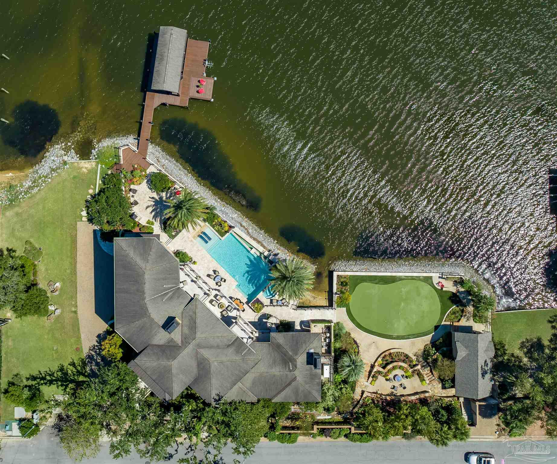 EXQUISITE LIVING at its finest in this stunning EAST HILL home with 230 feet of WATERFRONT on BAYOU TEXAR. Uniquely positioned on the Bayou to afford Panoramic Vistas from every vantage point, this elegant home was thoughtfully and meticulously designed to maximize water views. A superior level of craftsmanship is evident throughout this home which includes detailed stonework, travertine and white oak flooring, custom cabinetry, inlaid tiles can be found in the kitchen and baths. Truly a well-planned, spacious home, featuring three floors. Uppermost living space is comprised of three bedrooms with 3 en suite baths, office and laundry room. Then moving to the main floor with a master suite, laundry room, guest powder room and second bedroom/den with accompanying en suite bath. The main level gourmet kitchen features all high-end appliances such as Sub-Zero refrigerator/drawers, Wolf dual-fuel range/microwave/warming drawer, 2 dishwashers and Miele built-in coffee maker. The lower level boasts a second master bedroom/Mother-in-Law suite and additional fully appointed kitchen. A beautifully designed elevator services all 3 levels of the home. Other amenities on the lower level include family room, media/exercise room, 2 tv's, pool table as well as a lavish wine cellar. All levels have direct access to the outdoors for seamless transition to a beautifully designed multi-level outdoor waterfront space. The patio areas provide ample space for large gatherings and are perfect for entertaining with a high-end outdoor kitchen or relaxing with friends and family around the infinity edge pool w/ hot tub, fireplace or fire pit. This exceptional property includes additional recreational opportunities, private boat dock, four-hole putting green/synthetic grass, large storage house perfect for storing pool, fishing and lawn equipment. The 3 car garage has a convenient 220V charging outlet. This home incorporates all the latest technology to maintain efficiency and comfort.