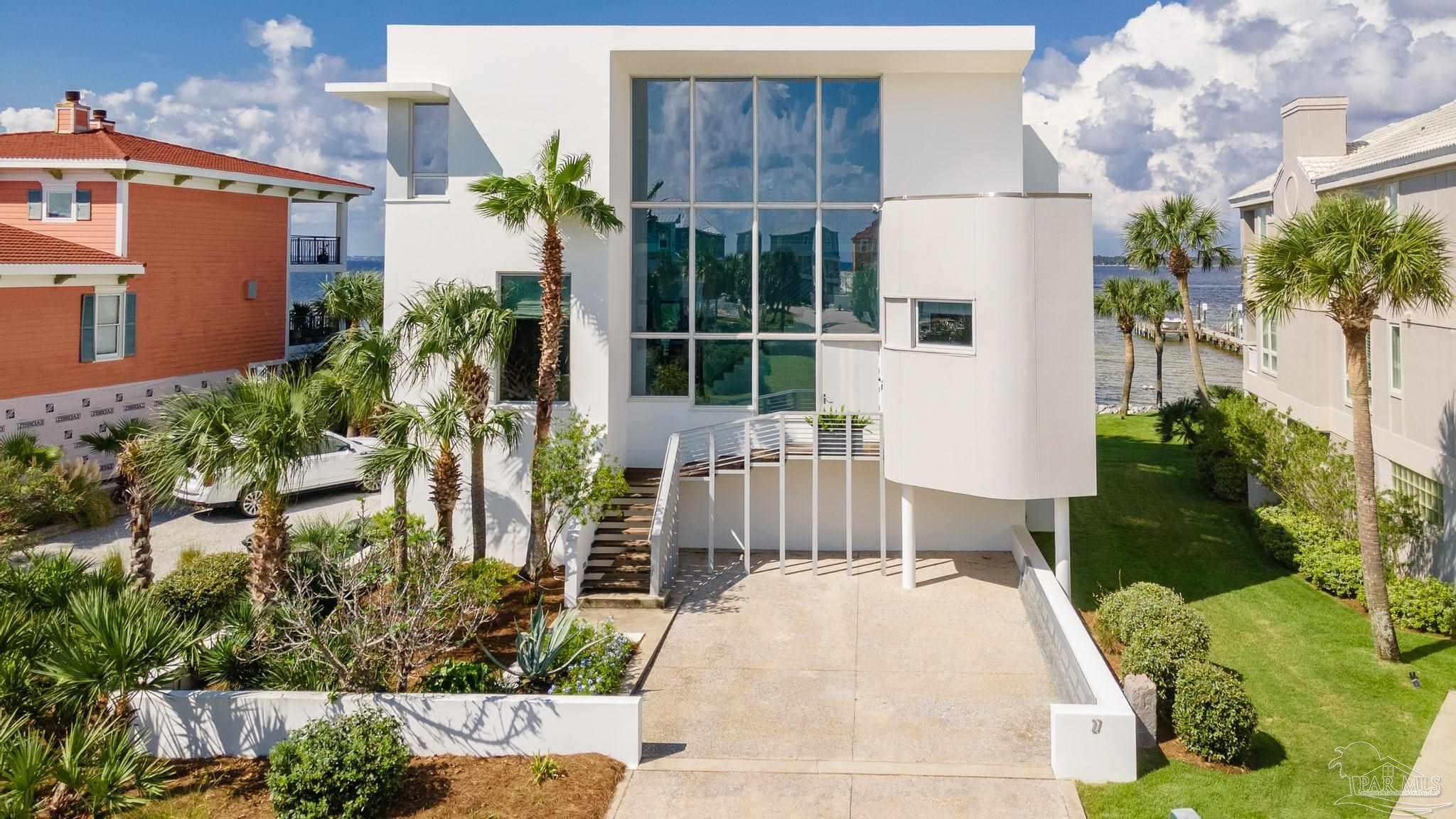 """An amazing coastal home that has no equal on Pensacola Beach in its design, construction and location.  Built on two lots, no expense was spared when this 4,864 sq ft, 4+ bedroom, 4 full bath home was built in the gated beach community of DeLuna Point.  Dramatic architectural details such as the glass catwalk spanning across the large entrance steel-railed stairway featuring full height windows and 2-story soaring ceilings provide an elevated sense of living throughout the home. As you walk into the open main floor living areas, you are greeted by views spanning the entire length of the home. The well-appointed kitchen features elegant cabinetry, professional appliances and butler kitchen behind an Italian glass tiled wall. The sliding doors create connectivity to the terrace providing additional entertaining space for outside dining & grilling and a relaxing space to capture the gentle island breezes while watching sunsets. The large 3rd floor primary bedroom offers a private balcony, fireplace, spa bathroom, and expansive water views. The 4th bedroom is appointed with 4 built-in bunkbeds, queen bed as well as its own ensuite. The lower level will also not disappoint.  In addition to the 3-car garage, there is an additional large bunk room.  When you walk outside, you find a large, covered area for relaxation & entertaining.  Additionally, there are 2 outdoor showers and additional parking in the two driveways.  The home is adorned with Australian cypress wood floors throughout, Italian glass tile, elegant lighting and soothing colors for sophisticated comfort, a gathering and entertaining place """"by the sea"""" to be shared with family and friends.  Built like a fortress, made of concrete and steel on an elevated concrete slab, there was no damage from hurricane Sally. The private dock with lift is also built at an elevated level. There is geothermal and an elevator to connect you to each level.Community Pool, dock, beach."""